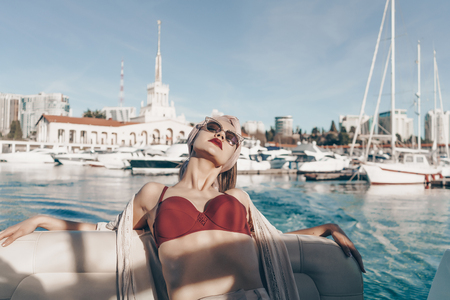 a luxurious rich woman in sunglasses relaxes on her white yacht in the sun, sails on the Caribbean sea