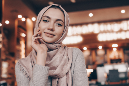 cute young muslim girl with headscarf sitting in an Arabian cafe, looking at camera and smiling
