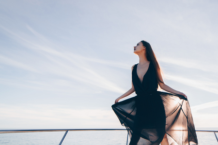 a luxurious young girl in black summer clothes enjoys sea voyage and vacation Stok Fotoğraf - 101854732