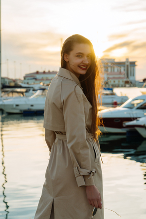 smiling beautiful young girl with long hair in a beige coat posing by the sea at sunset Standard-Bild