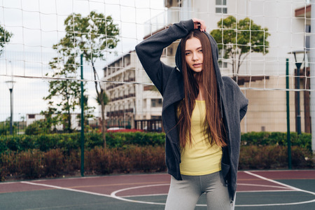stylish long-haired girl trains on a sports ground, leads an active lifestyle Stok Fotoğraf
