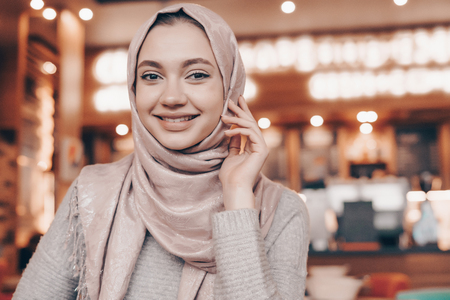 beautiful Muslim girl with a headscarf sitting in a cozy restaurant, smiling and waiting for her food