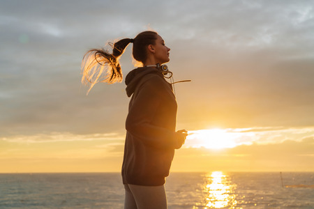 confident long-haired athletic girl jogging by the sea at sunset
