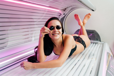smiling young brunette girl sunbathing in horizontal sunbed, wearing goggles