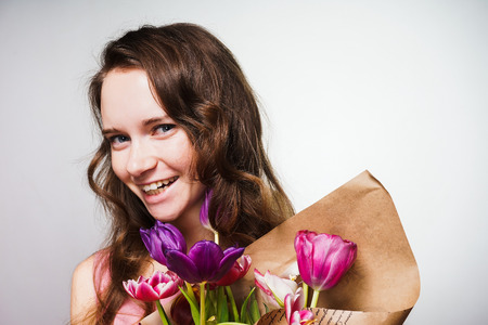 beautiful smiling woman enjoying the spring, holding a bouquet of fragrant flowers Stockfoto