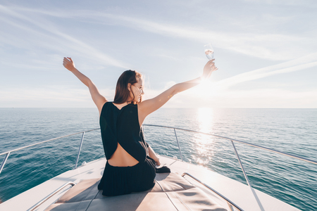 joyful young girl sits on a white boat, drinks champagne and enjoys vacation and travel Stok Fotoğraf - 103183542