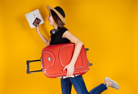 happy young girl in a hat rides in a long-awaited vacation abroad, with a large red suitcase Stock Photo