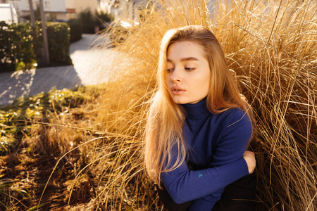 young beautiful blond model girl in fashionable blue sweater posing in the sun on the streets of the city Stock Photo