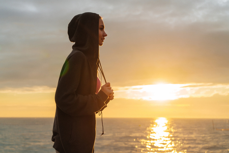 active confident girl in a sweater is engaged in jogging at sunset by the sea, preparing for competitions