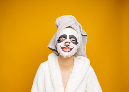 a nice girl with a towel on her head and a white bathrobe gown looks after herself, on her face a moisturizing mask with a panda face Stock Photo