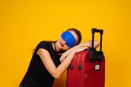 nice girl in a black T-shirt is sleeping on a red suitcase, in front of a mask for sleeping, waiting for the plane