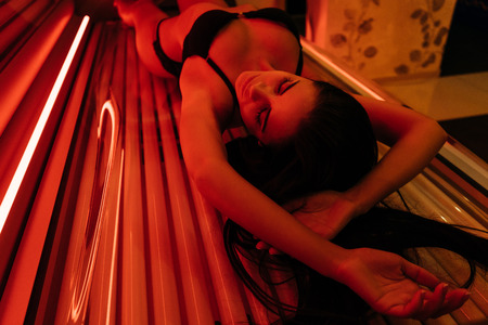 slender sexy girl brunette sunbathing in a horizontal solarium under the ultraviolet rays
