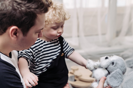 caring young dad playing with his little fair-haired son, have fun