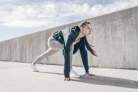 ragazza sportiva fiduciosa in piedi all'inizio, preparata a correre una maratona all'aperto