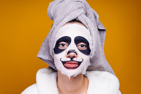 charming girl after shower, posing, on face moisturizing mask with muzzle of panda Stock Photo