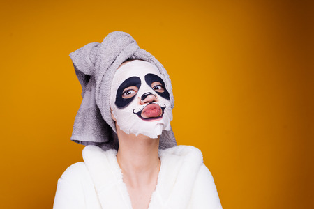 a funny young girl with a towel on her head and a white robe takes care of herself, on her face a mask with a panda face Stock Photo