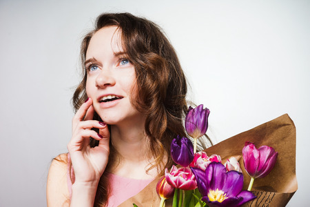 charming blue-eyed woman smiling. holds a large bouquet of flowers