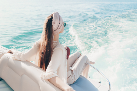 stylish young woman enjoys a rich life and sea voyage on a yacht Banco de Imagens