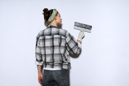 young slender girl in a plaid shirt leveling the walls with a spatula