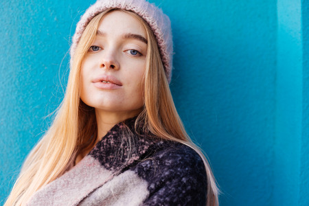 beautiful blue-eyed girl blonde in a warm hat posing against a blue wall background Stok Fotoğraf