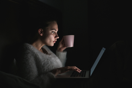 serious young girl working on laptop late at night, drinking coffee