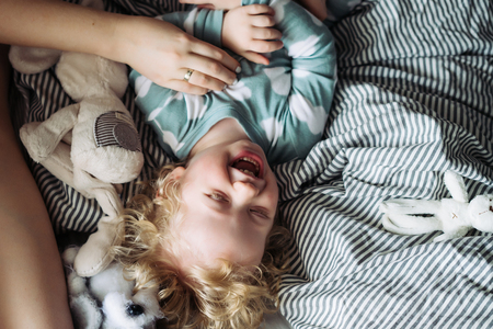 a small fair-haired boy in blue pajamas lies on the bed next to his mother, laughs, have fun Imagens