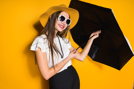smiling confident long-haired girl model in hat and sunglasses holds umbrella and posing on yellow background