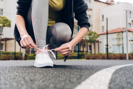 a sporty girl in gray leggings ties up her shoelaces on her white sneakers, leads an active lifestyle