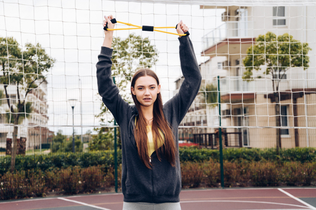 confident slender girl does exercises for hands on the sports ground, leads an active lifestyle