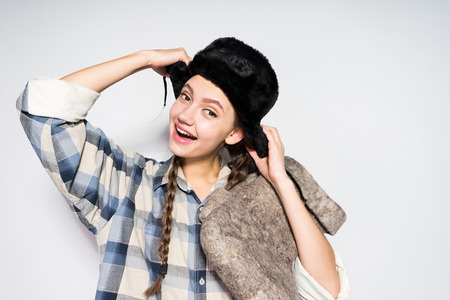 a funny Russian girl with pigtails smiles and holds warm gray felt boots, a black fur hat on her head