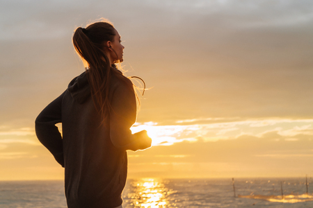 stubborn long-haired girl runs around the sea at sunset, wants to lose weight