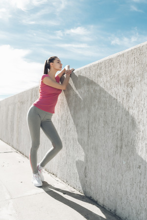 high slender girl with a beautiful figure resting after a difficult workout under the blue sky