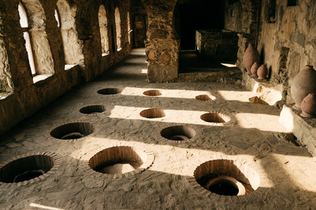 stone old room with holes in the floor for wine, alcohol industry