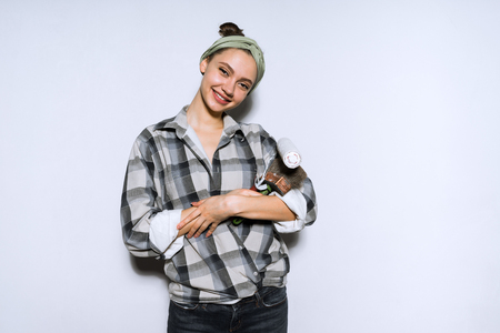 beautiful girl painter in a plaid shirt smiling and posing, holding a brush and roller for painting the walls