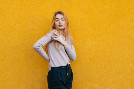 confident stylish girl with long blond hair posing against a yellow wall, street fashion