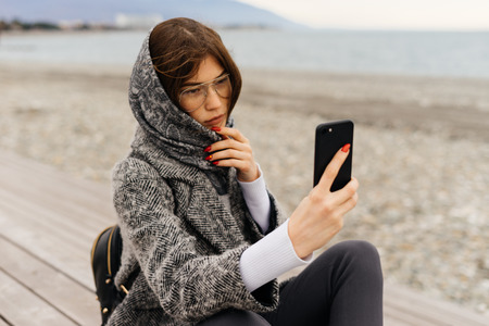 stylish, daring dark-haired girl in a gray coat and glasses takes pictures of the seascape Stock Photo