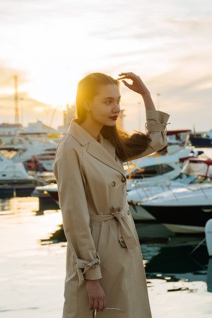 luxurious stylish girl in a beige coat is waiting for her yacht in the port of a car at sunset