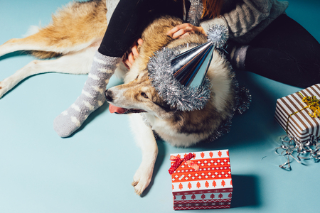 woman sitting on the floor with her dog next to New Years gifts