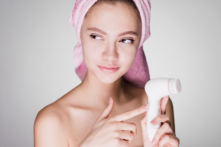 woman on a white background holds a brush for deep cleaning Фото со стока