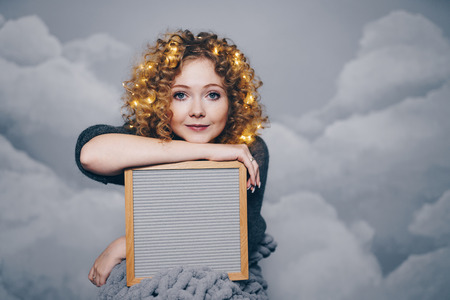 a young woman is sitting on the background of clouds and is holding a writing board, a garland in her hair