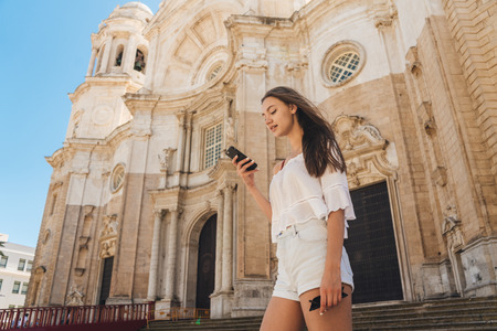 Tourist girl traveling alone, looking for something in the smartphone on the background of the ancient cathedral in Europe. looks into the navigator. Catedral de Santa Cruz de Cdiz
