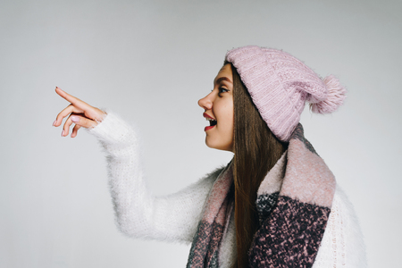 Surprised girl in winter clothes looks away and shows something with a finger.