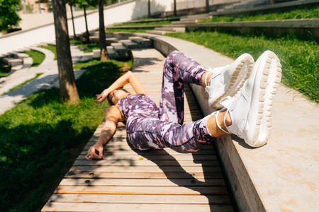 Young woman tired after workout on the street, lying on a bench in the park 写真素材
