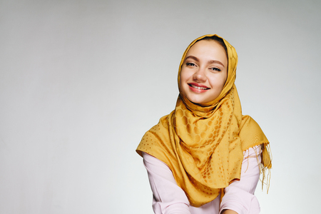 Happy girl in muslim scarf on white background smiling