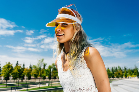 Funny young woman in white lace blouse and cap in the park on a sunny day