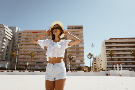 Happy tanned girl on vacation holding hat, strong wind, white sand, vacation 写真素材