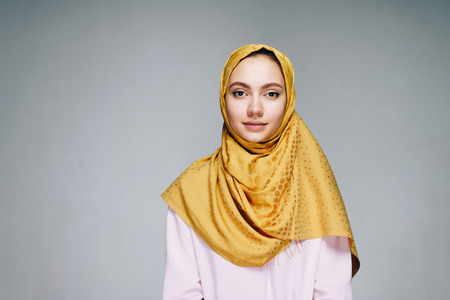 A young woman in a Muslim headscarf and clothes calmly looking into the camera on a white background. Studio 写真素材