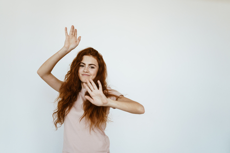 Cheerful girl with long red hair is dancing on a white background