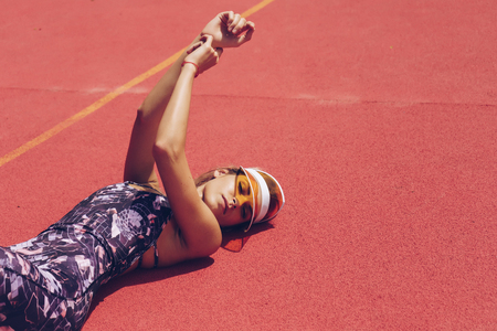 Sports fashion woman lying on a red background, on her head a yellow tennis cap from the sun