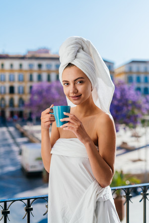 Beautiful young woman is having breakfast in the morning on the balcony after a shower. Drinking coffee from a mug